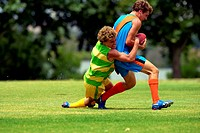player tackles his opposition in football game