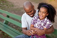 Father and daughter on park bench laughing.