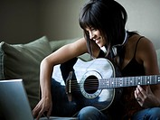 Woman sitting on sofa with laptop and guitar
