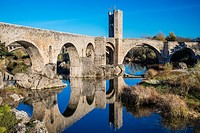 The old Romanesque stone bridge reflected into the Fluvià river, Besalú, Catalonia, Spain