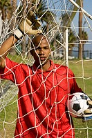 Player standing in nets holding soccer ball