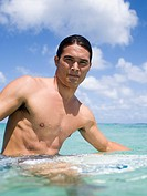 Man sitting on surfboard in water smiling