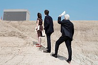 Three businesspeople in construction site looking at building, side view