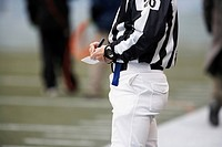 American football referee writing notes, mid section