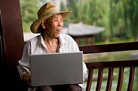 Mature man with straw hat and laptop outdoors