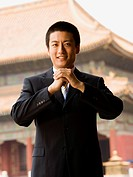 Businessman smiling with hands in greeting with pagoda in background