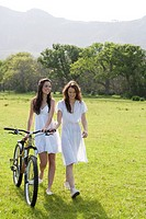 Two woman pushing bicycle through field