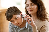 Mother taking temperature of son by ear