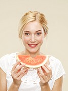 woman smiling holding a slice of watermelon