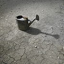 Watering can on cracked mud.