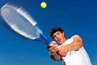 Tennis player focused on ball.