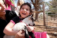 Mature woman and girl 4_5 with baby goat, laughing, outdoors