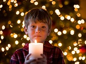 boy at christmas holding a candle