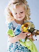little girl holding an armful of her toys