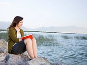 woman sitting by a lake writing in a journal