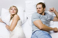 couple with marriage problems lying in bed