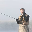 man fishing in a river on his cell phone