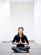 woman sitting on the floor in her workplace meditating