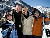 Portrait of a mid adult couple and their children holding snowboards