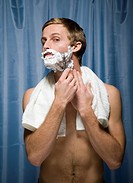 Close_up of a young man shaving