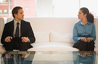 Businessman and a businesswoman sitting on a couch and looking at each other