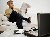 Businessman sitting on a couch and reading a newspaper