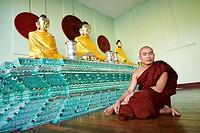 A burmese buddhist monk sit in a praying room inside the Shwedagon Pagoda complex  Yangon  Myanmar