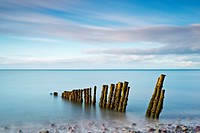 Wooden groynes on a beach at low tide, at dusk