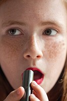 A young girl putting on lipstick