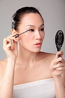 Beautiful Asian woman using mascara brush