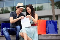 Young couple looking in shopping bags outdoors.