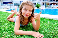 children girl lying on pool grass in summer