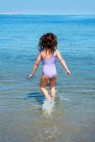 brunette little girl running into beach water
