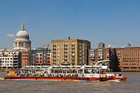 St Paul's Cathedral near the Millennium Footbridge, pedestrian bridge over Thames with Thames Clippers boat, City of London, from Bankside, London, Un...