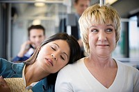 Close_up of a young woman sleeping on a mature womans shoulder