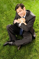 High angle view of a businessman with hugging a toy sitting on a grass