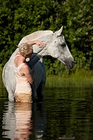 Young woman with a Hanoverian horse in a lake