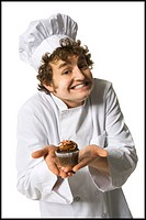 Portrait of a chef holding a muffin