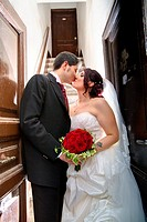 Wedding couple kissing on a doorstep