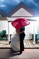 Wedding couple kissing underneath a red umbrella Ostia Rome Italy
