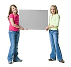 Two young girls holding a blank sign