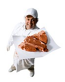 Butcher with steaks smiling