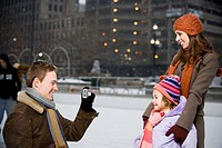 Man taking picture of woman and girl outdoors in winter