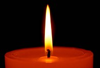 A candle burning with a bright flame on a black background