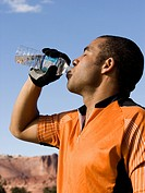 Profile of man drinking bottled water outdoors