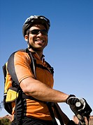 Male cyclist with helmet outdoors smiling