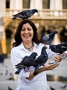 Woman in public square feeding pigeons and smiling