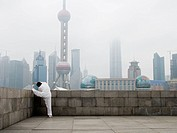 Man doing tai chi outdoors with city skyline in background