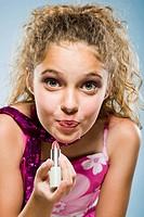 Closeup of girl applying lipstick