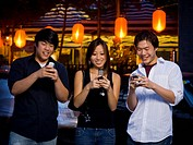 Three people with cell phones outdoors at night smiling